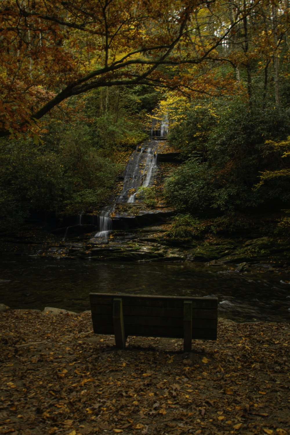 brown wooden bench near water falls during daytime