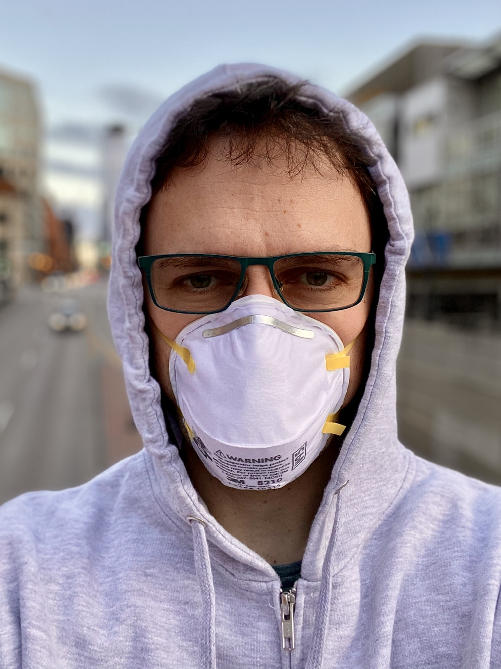woman in gray hoodie wearing white face mask