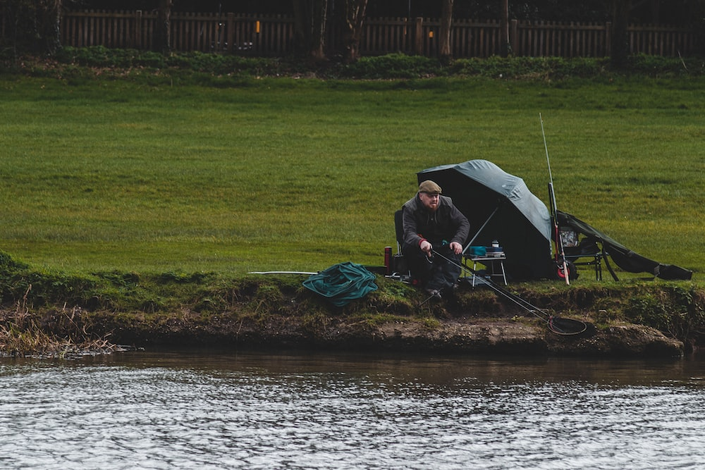 man in black jacket sitting on green grass field near body of water during daytime