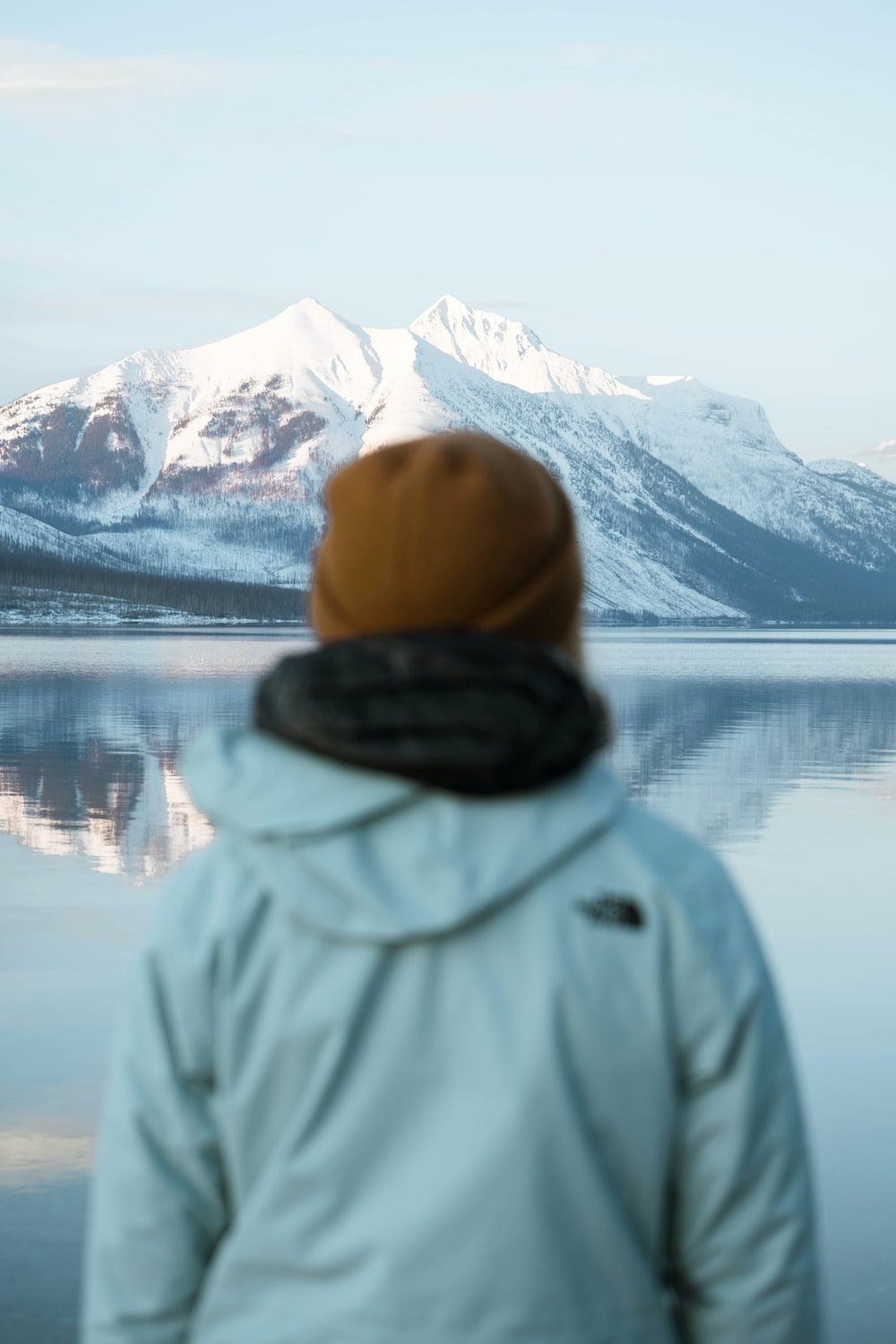 person in gray hoodie standing near lake during daytime