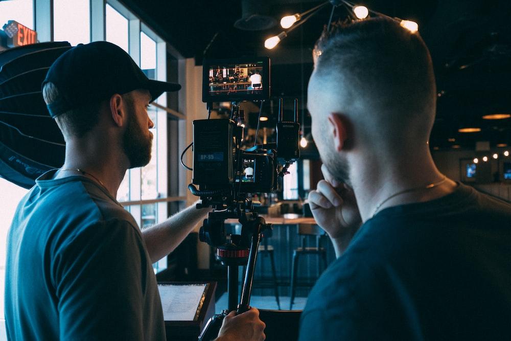 man in blue crew neck t-shirt using black video camera