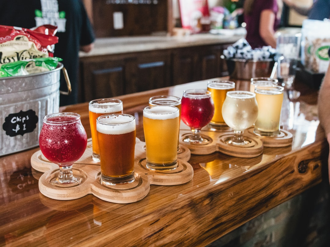 Multiple wooden platters with samples of assorted beer, cider, and mead.