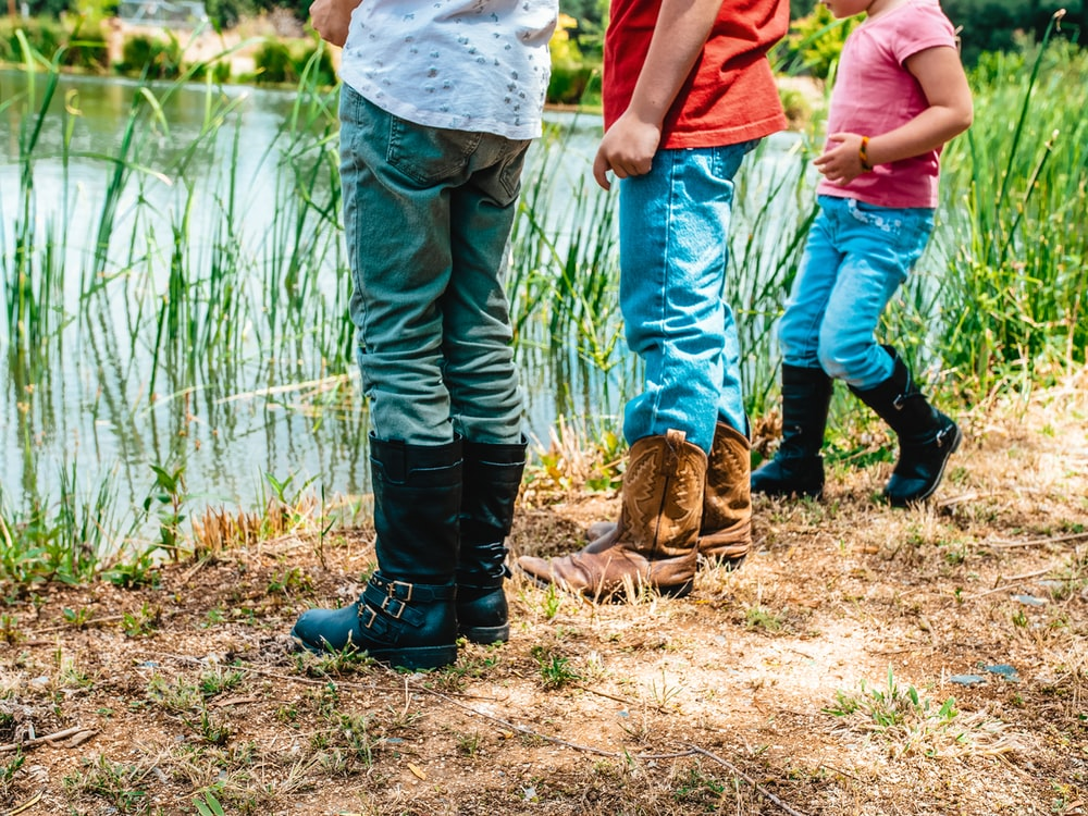 man in blue denim jeans and brown leather boots standing beside body of water during daytime