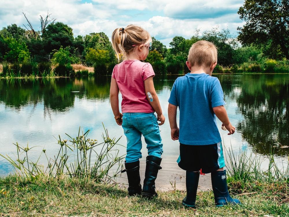 2 boys standing on green grass near lake during daytime