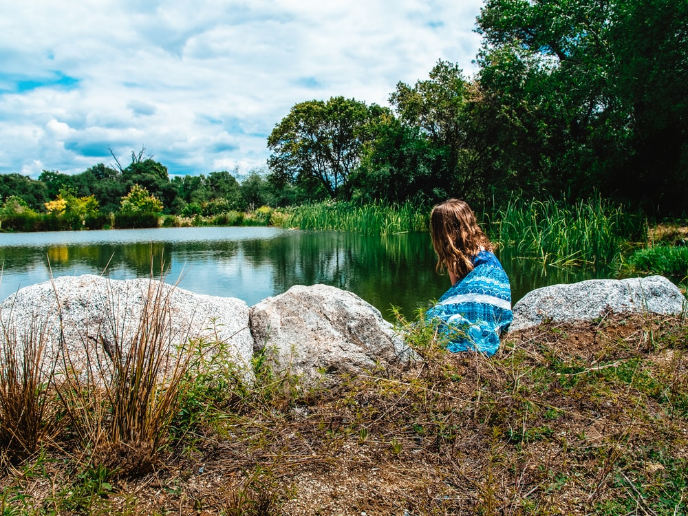 woman in blue and white dress sitting on rock near lake during daytime