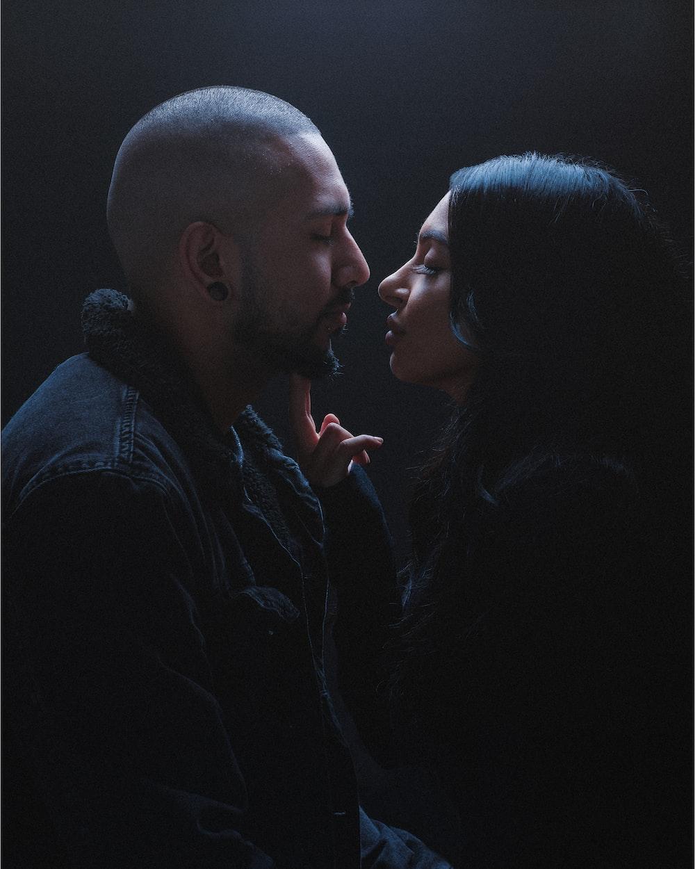 man in black dress shirt kissing woman in black dress
