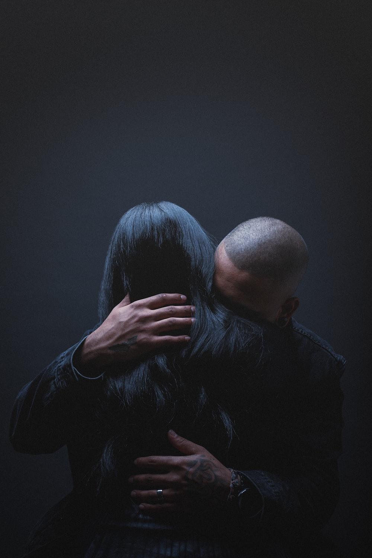 man in black dress shirt hugging woman in black long sleeve shirt