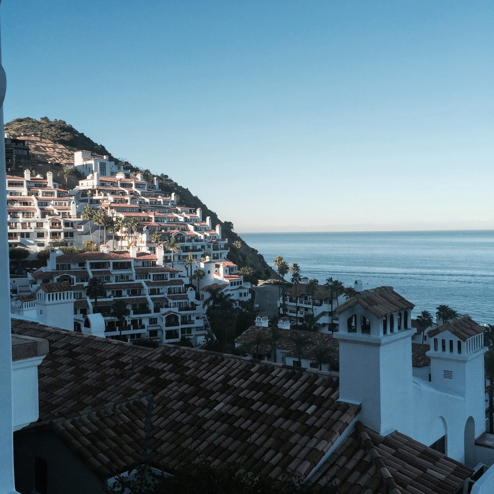 white and brown concrete houses near sea during daytime