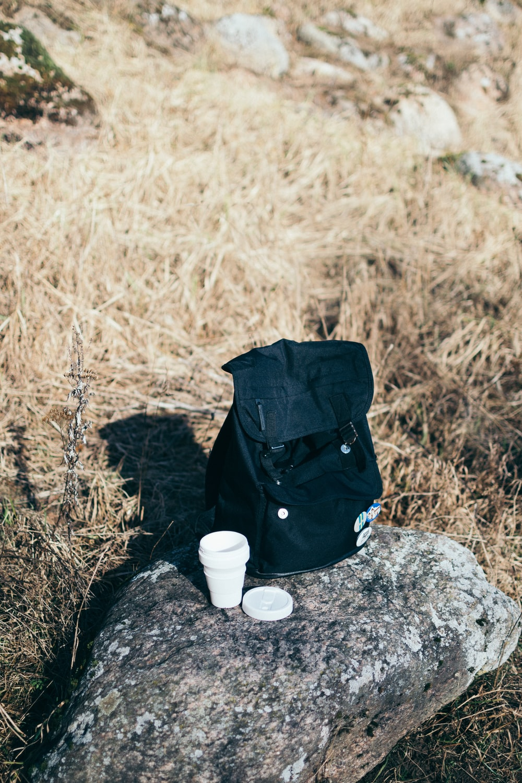 black backpack on gray rock