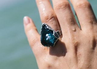 blue and black stone on persons hand