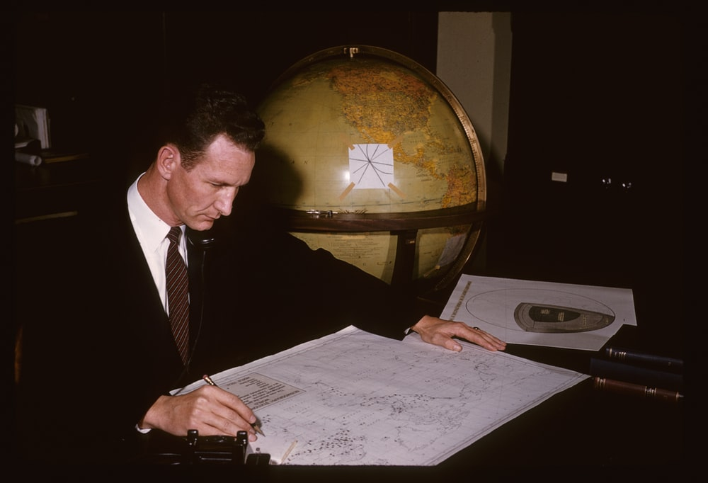 man in black suit jacket writing on white paper