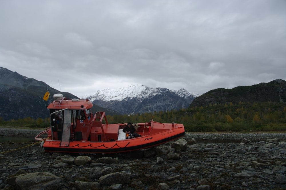 red boat on body of water near mountain during daytime