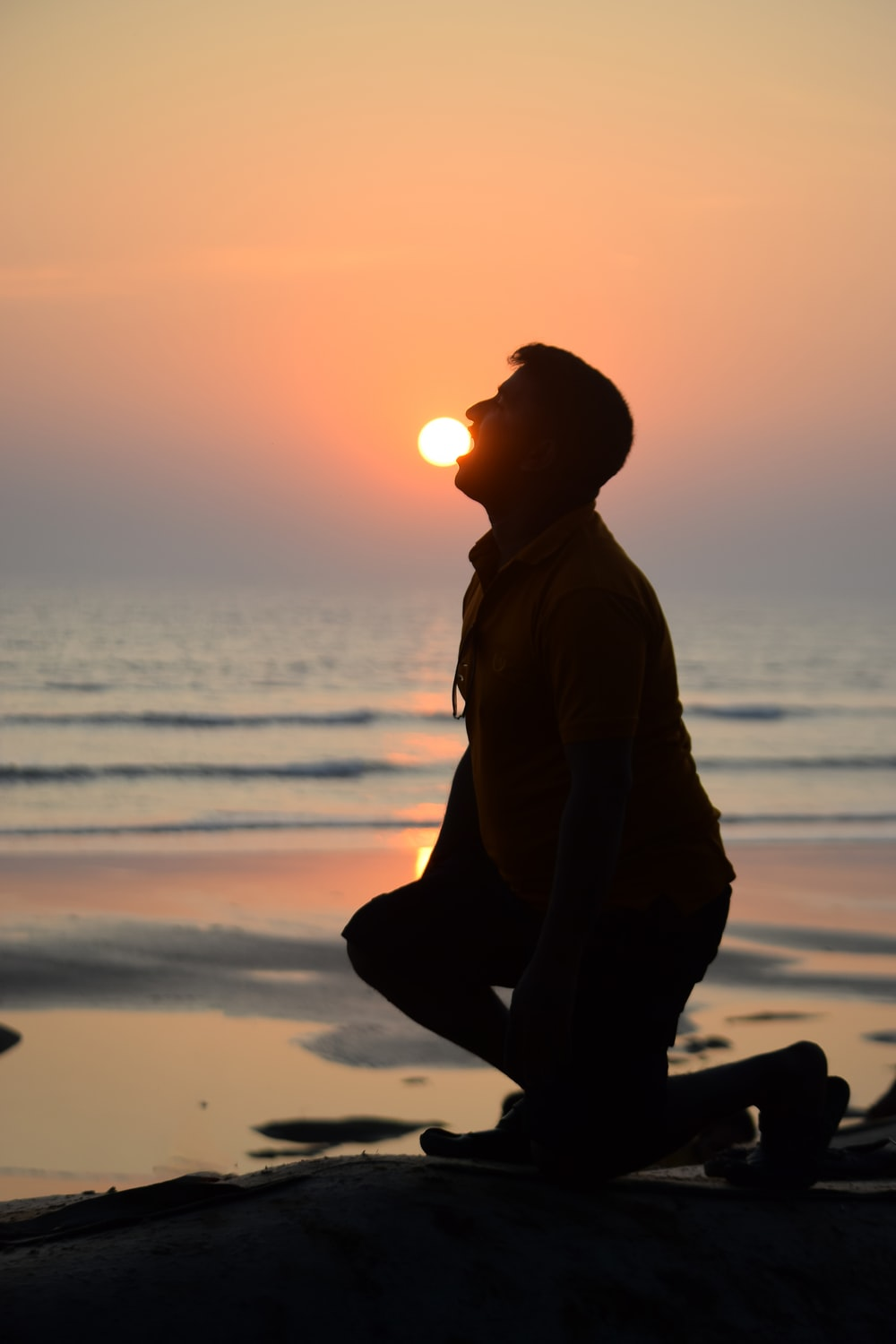 silhouette of man sitting on beach during sunset