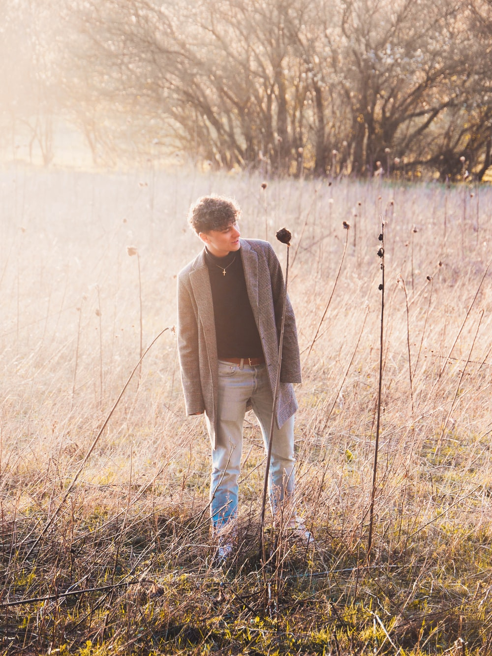 man in brown coat walking on grass field during daytime