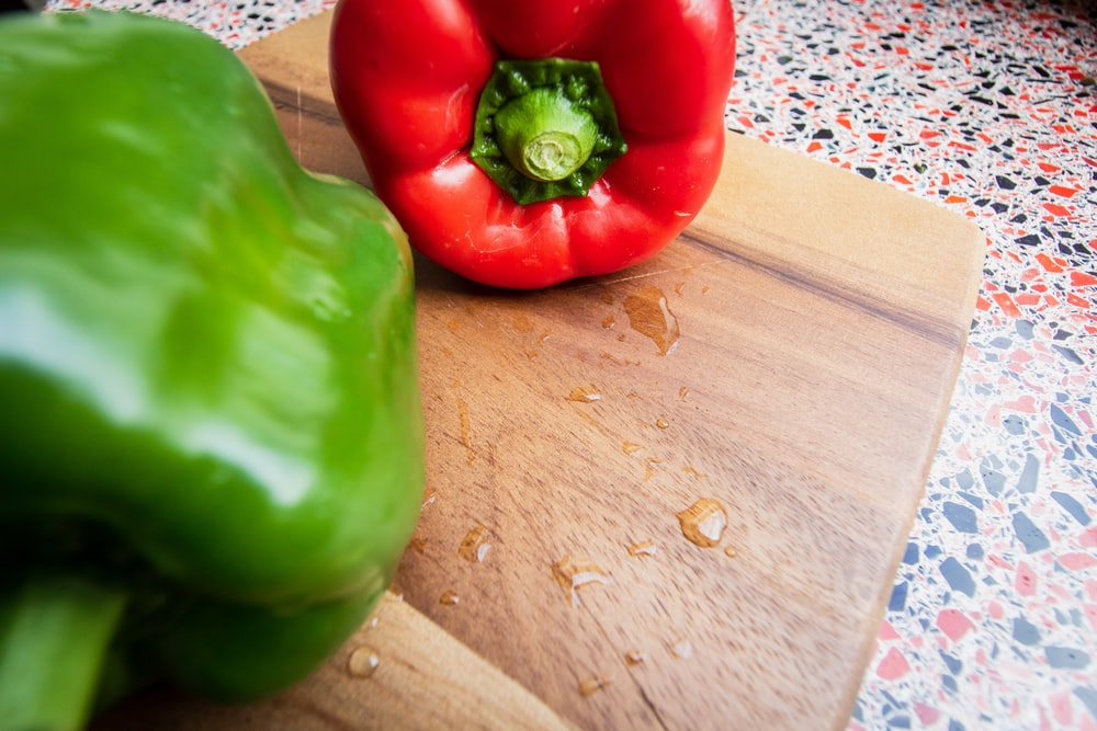 green bell pepper on brown wooden table