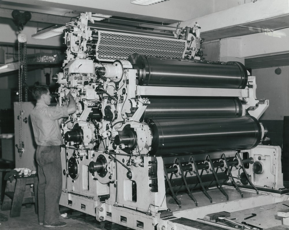 man in white shirt standing beside green machine