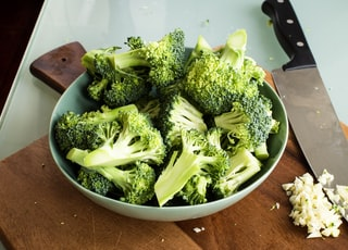 green broccoli on brown wooden chopping board