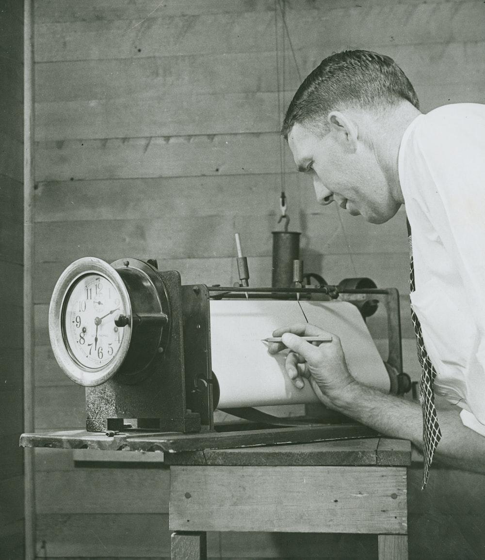 man in white shirt holding a gray machine