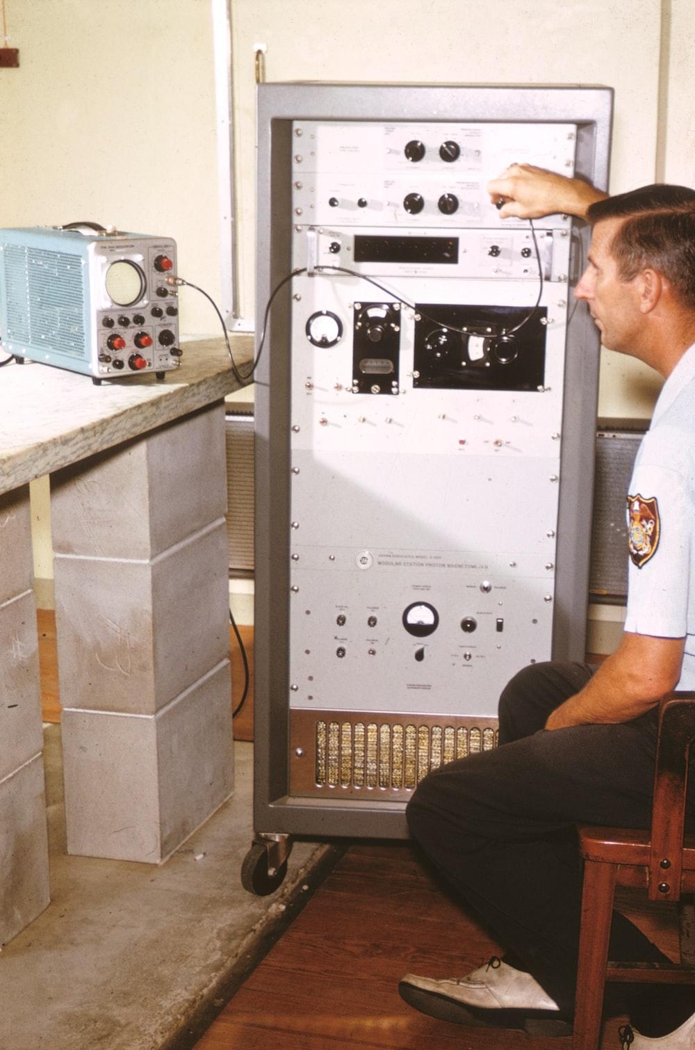 man in white t-shirt sitting beside gray audio mixer