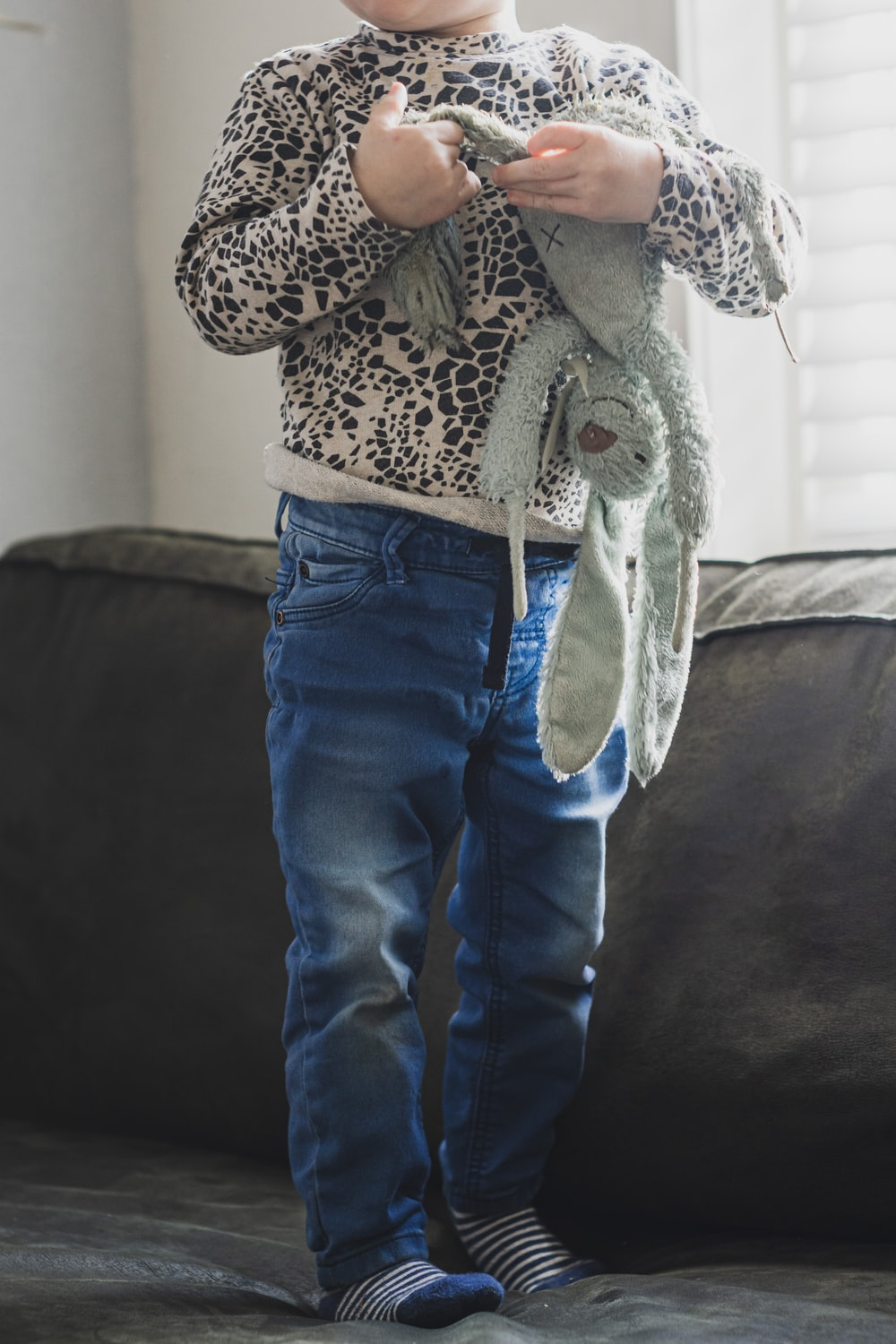 person in blue denim jeans and brown and white leopard print coat standing on black textile