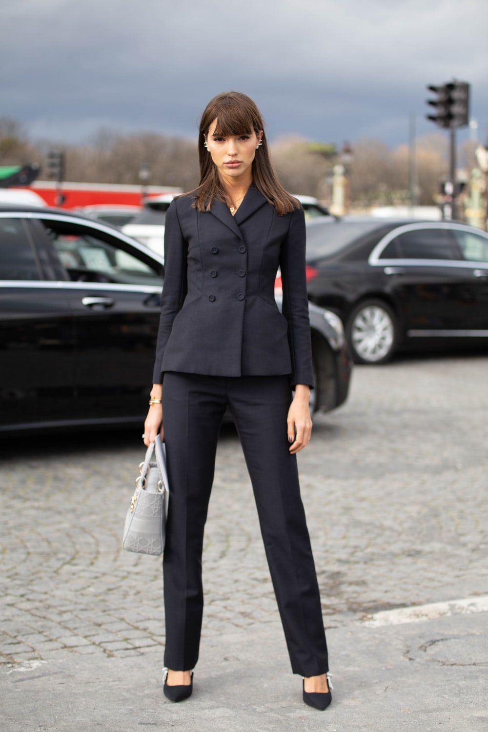 woman in black blazer and black pants standing on road during daytime
