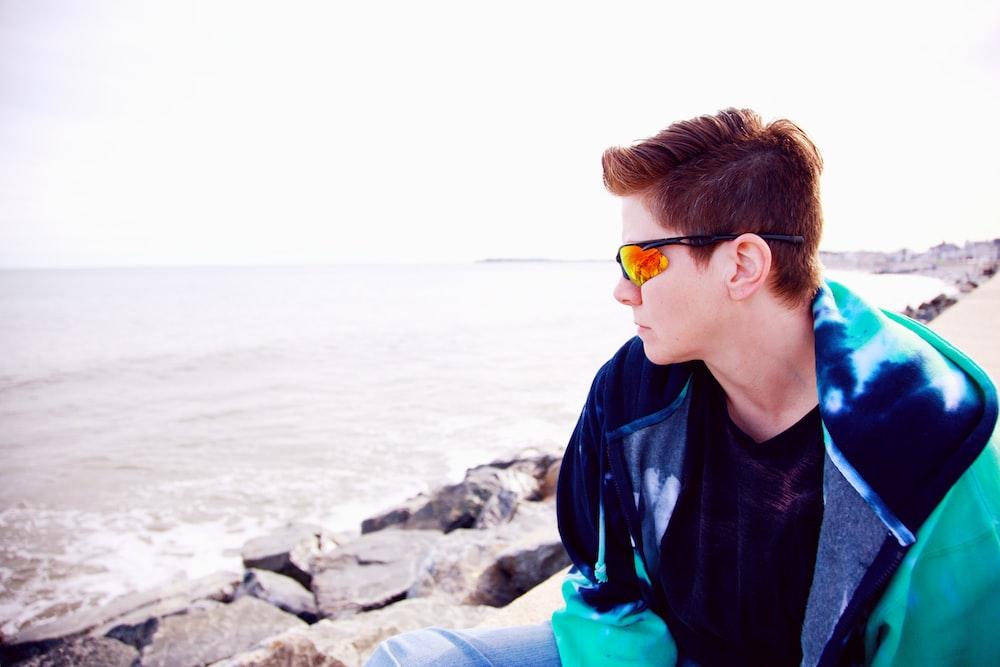 boy in blue jacket wearing sunglasses sitting on rock near sea during daytime
