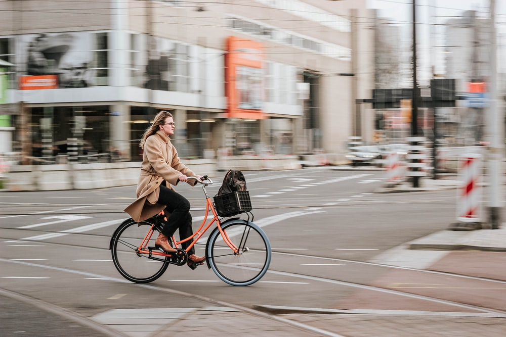 woman in brown coat riding on black bicycle on road during daytime