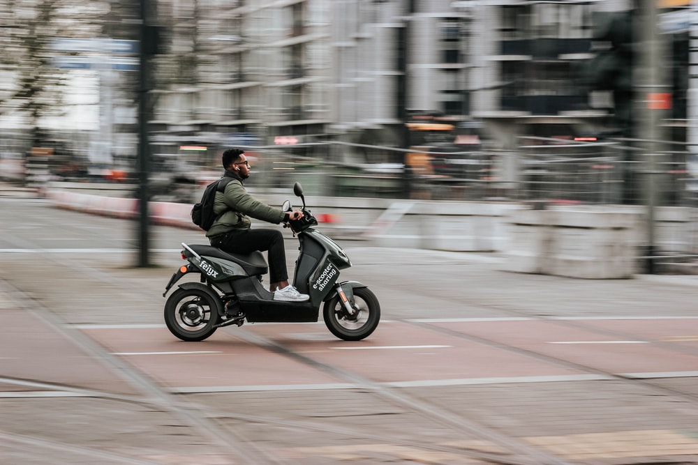 man in green jacket riding motorcycle on road during daytime