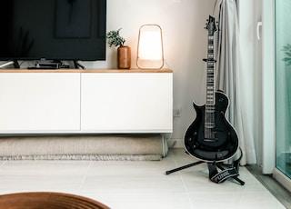 black flat screen tv on white wooden tv rack