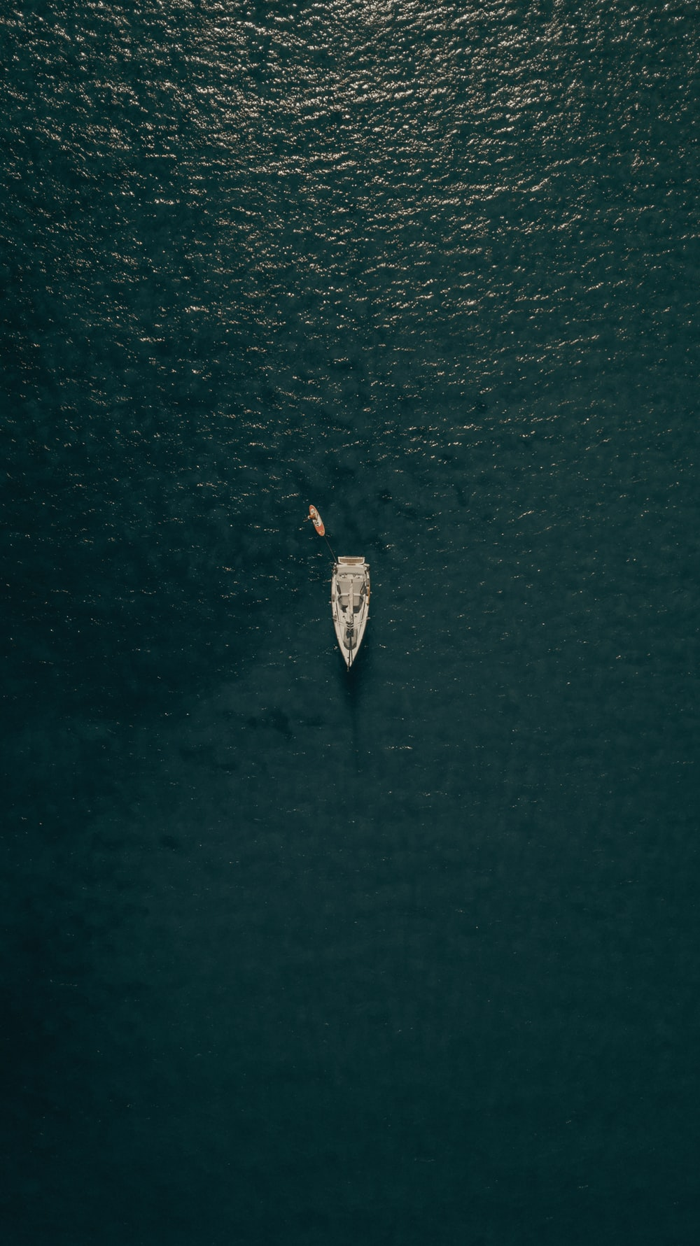 aerial view of person in white shirt riding on white boat on water during daytime