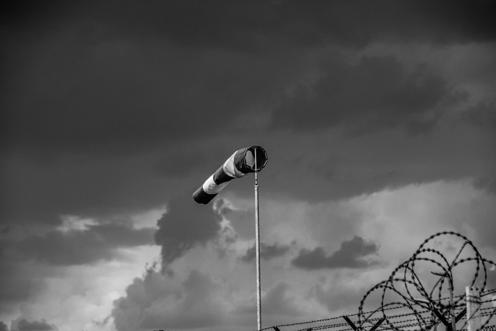 grayscale photo of light post under cloudy sky