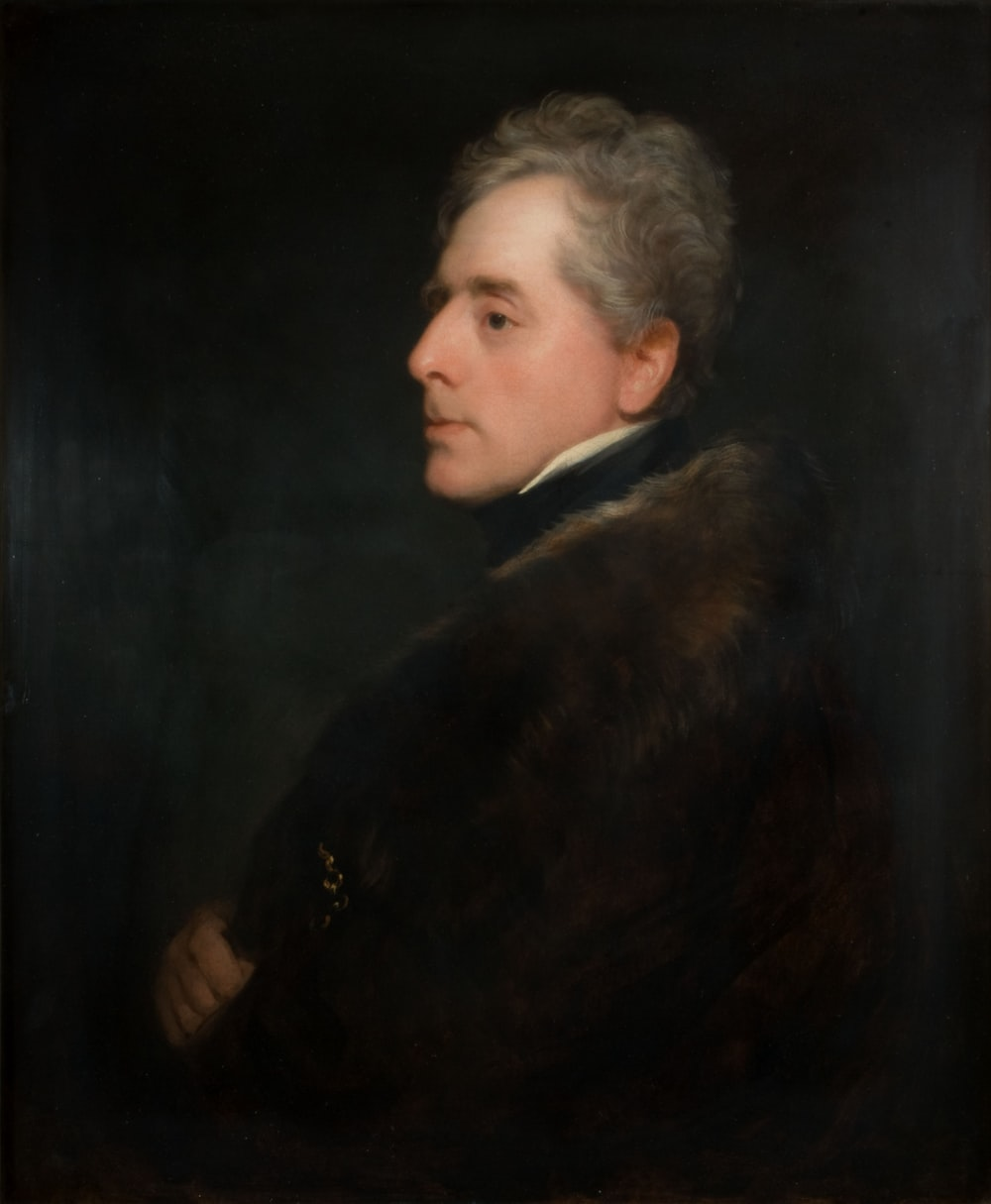 man in black and brown coat painting