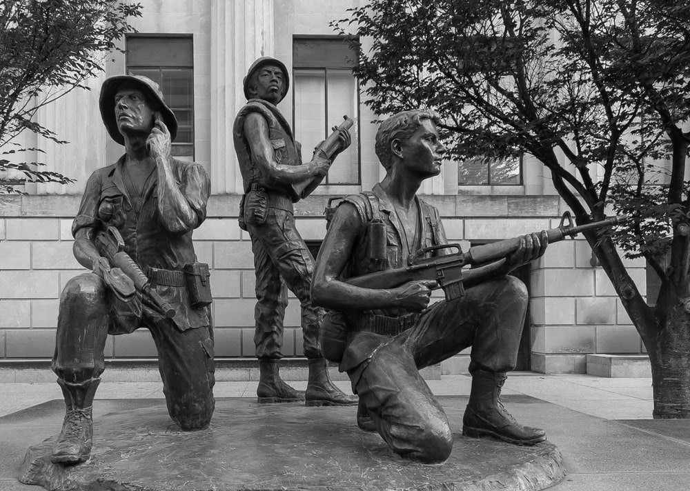 grayscale photo of 2 men and woman statue