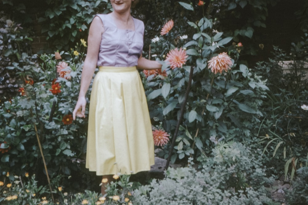 girl in yellow sleeveless dress standing beside red flowers