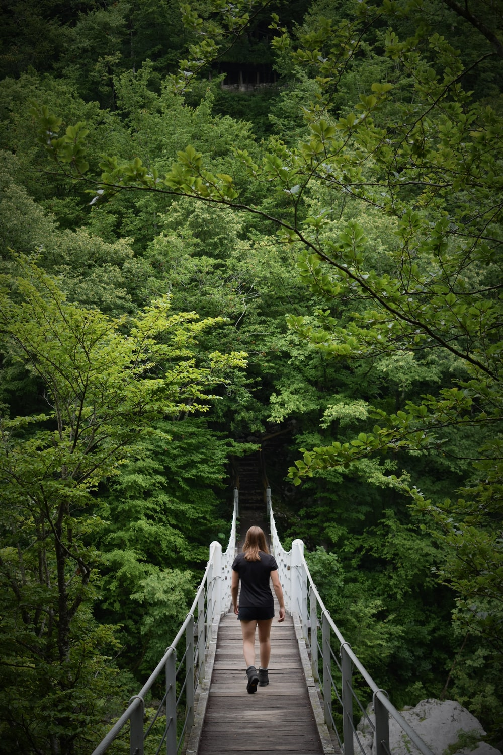 woman in white dress walking on hanging bridge