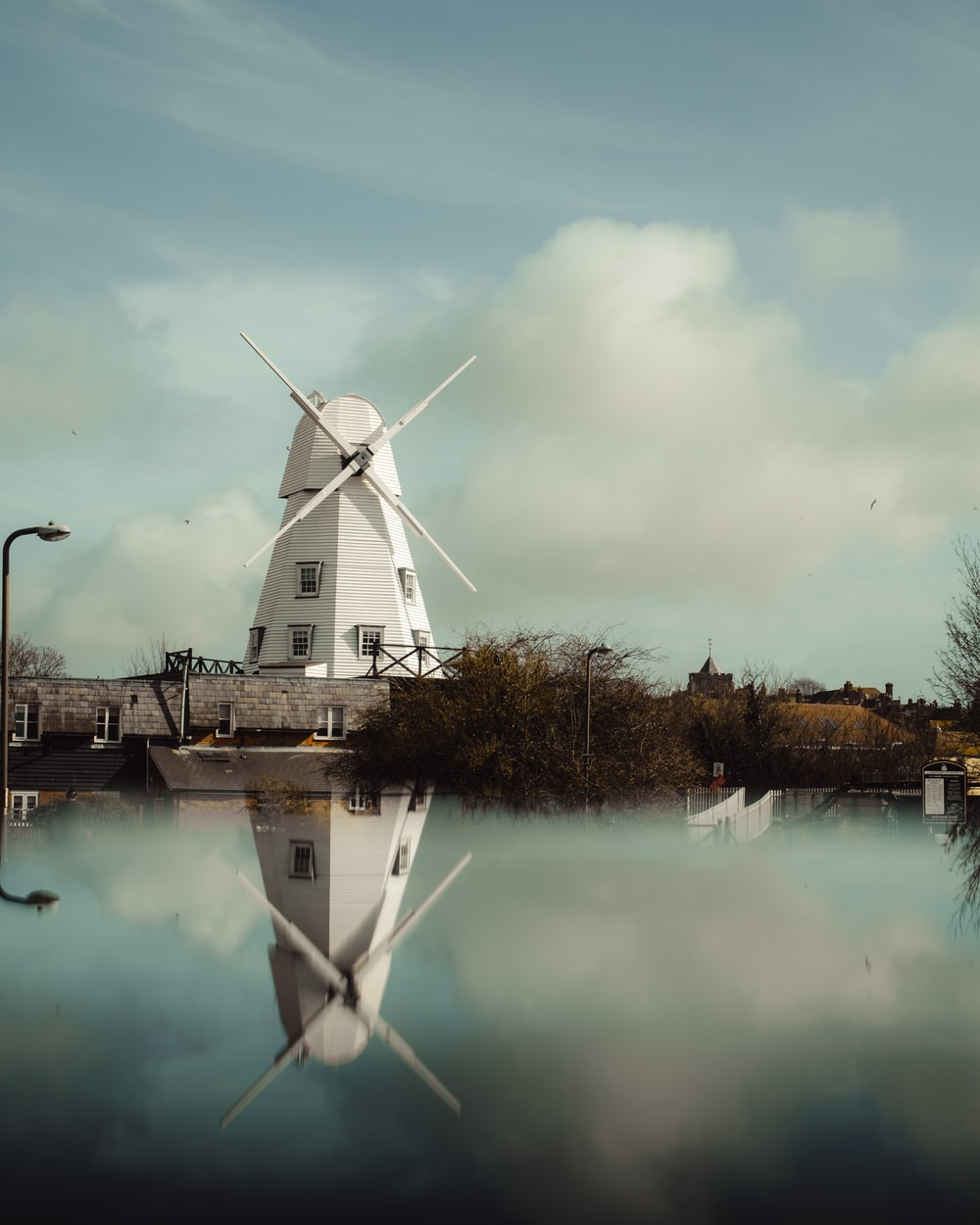 white windmill near body of water during daytime