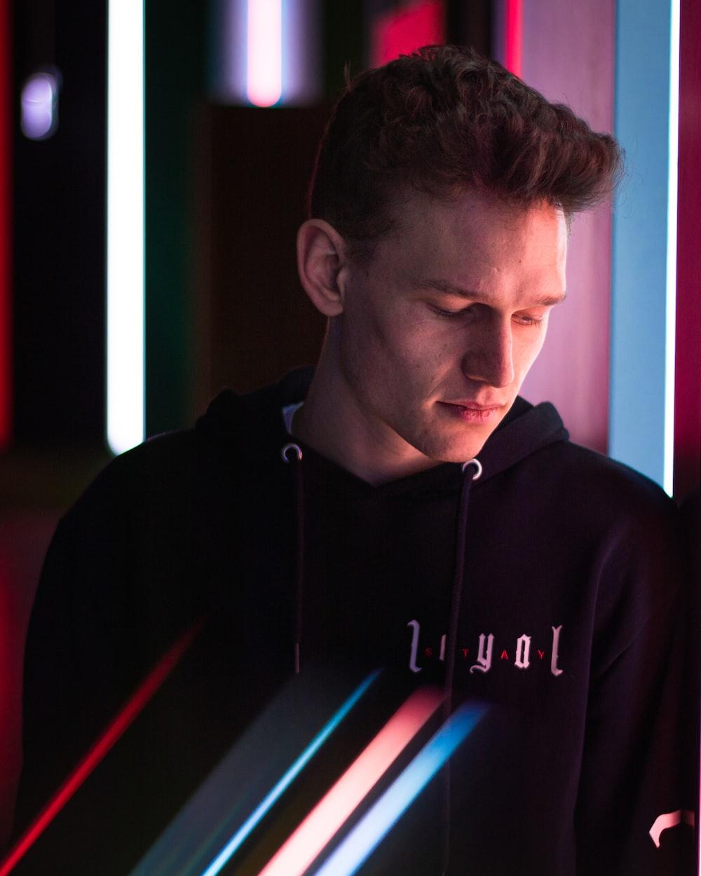 man in black hoodie looking at the window