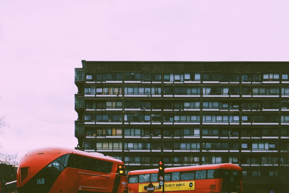orange bus near black concrete building during daytime