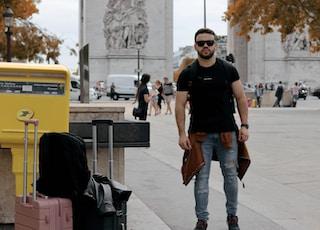 man in black crew neck t-shirt and blue denim jeans standing on sidewalk during daytime