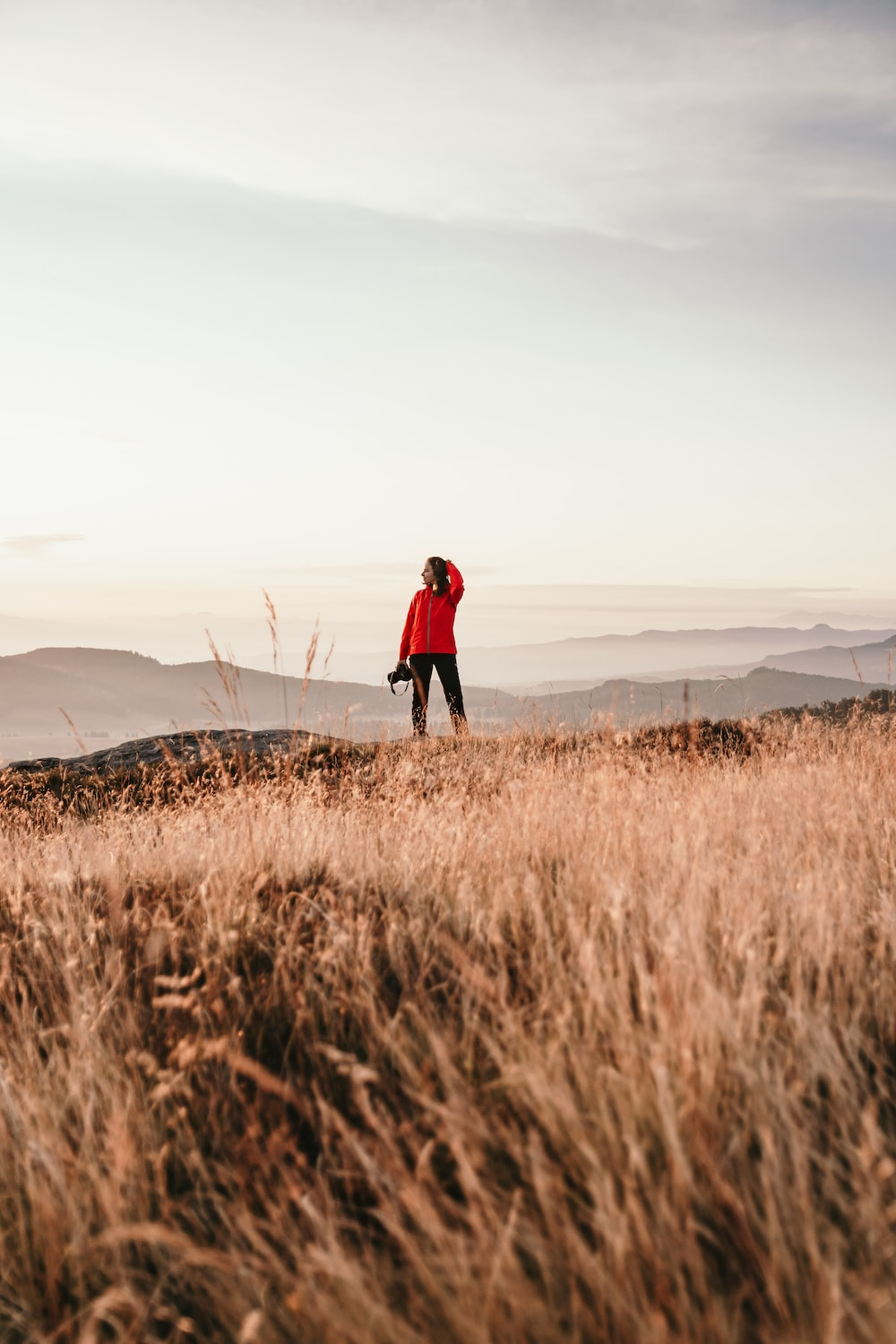 person in red jacket walking on brown grass field during daytime