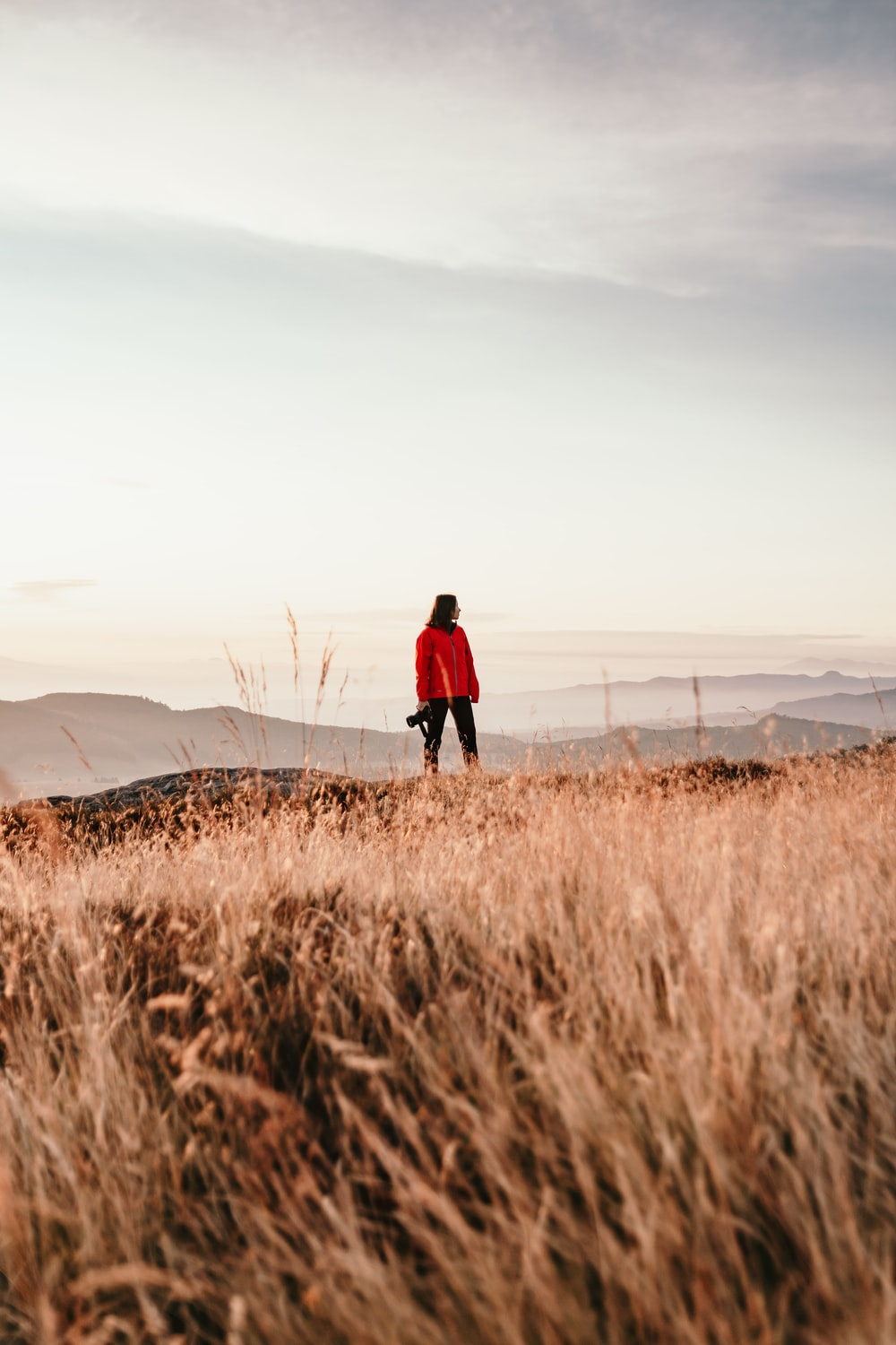 man in red jacket walking on brown grass field during daytime