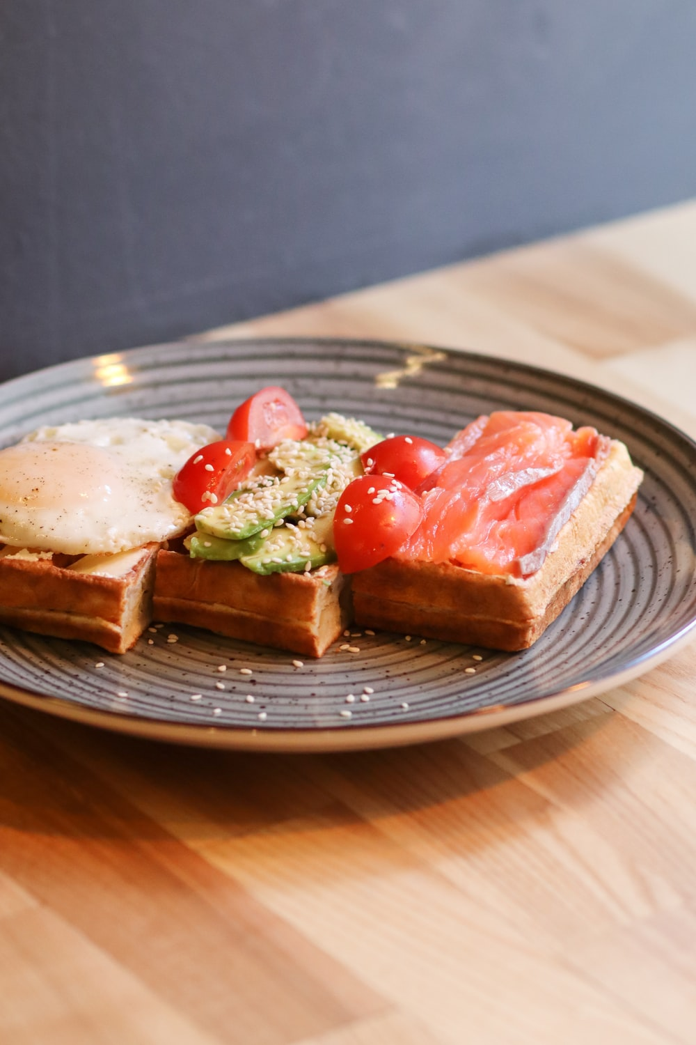 sliced bread with tomato and green vegetable on brown wooden round plate