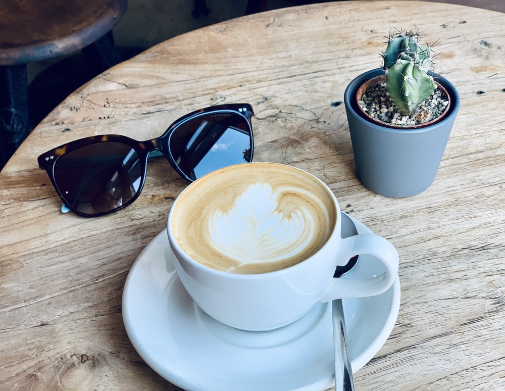 white ceramic cup with saucer beside black sunglasses on brown wooden table