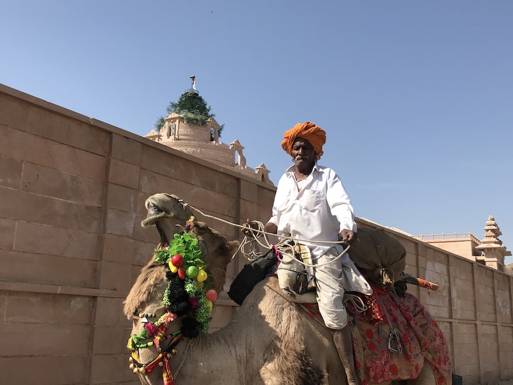 man in white robe riding on brown horse during daytime