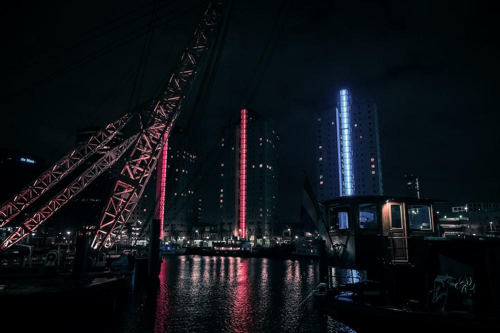red metal bridge near city buildings during night time