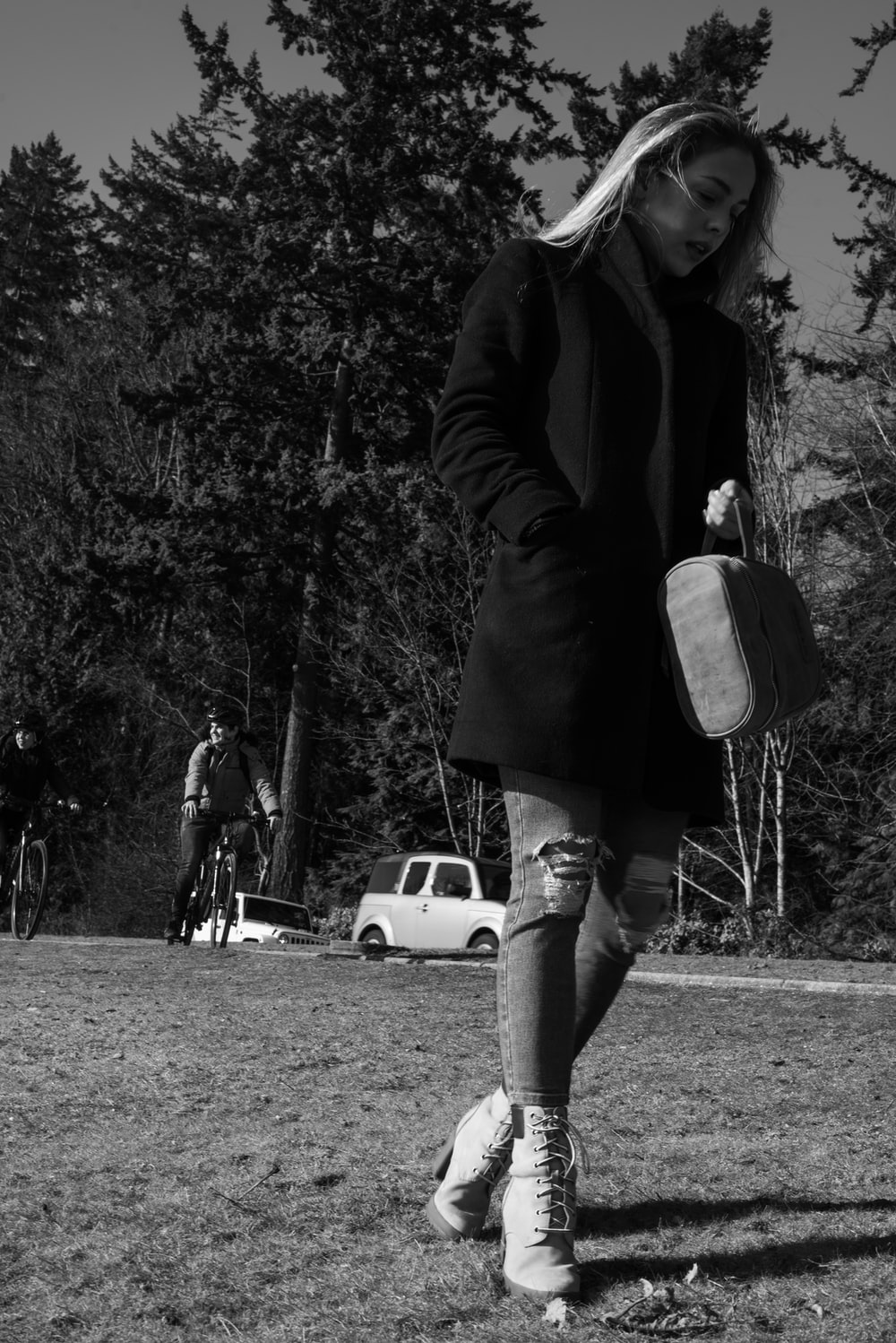 grayscale photo of woman in black coat and white skirt carrying white handbag