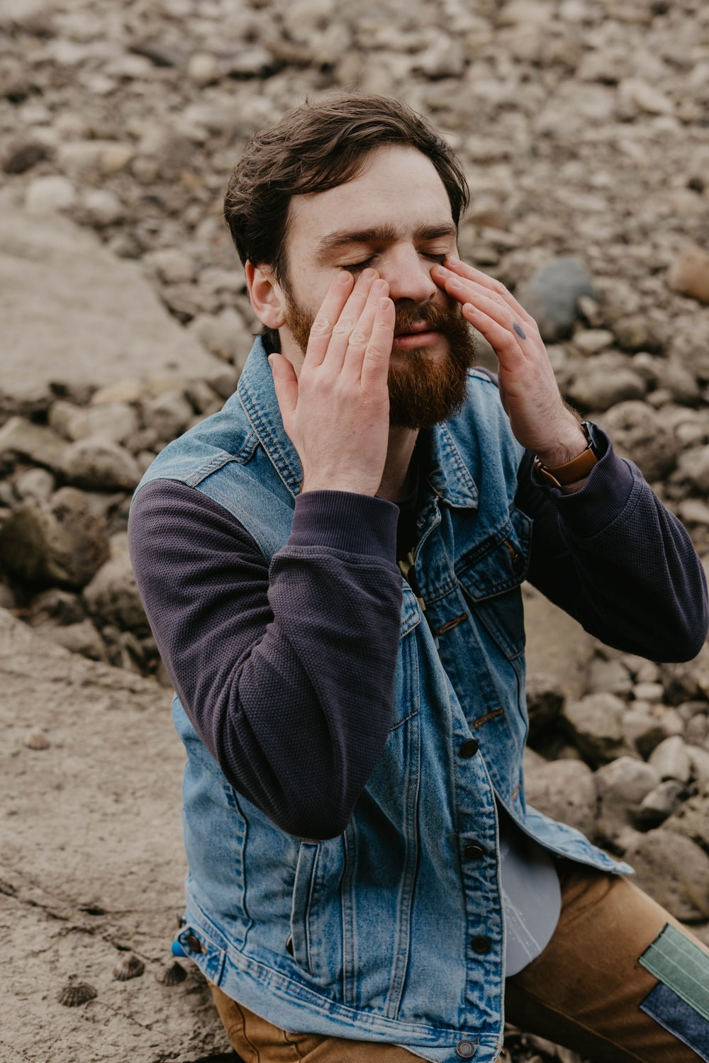 man in blue denim jacket covering his face with his hand