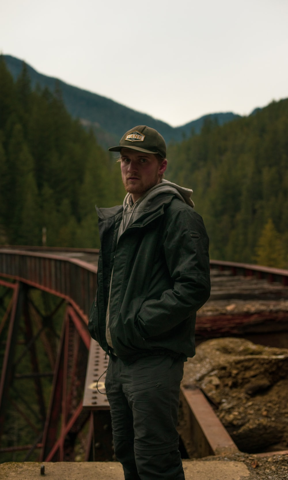 man in black jacket standing on brown rock during daytime