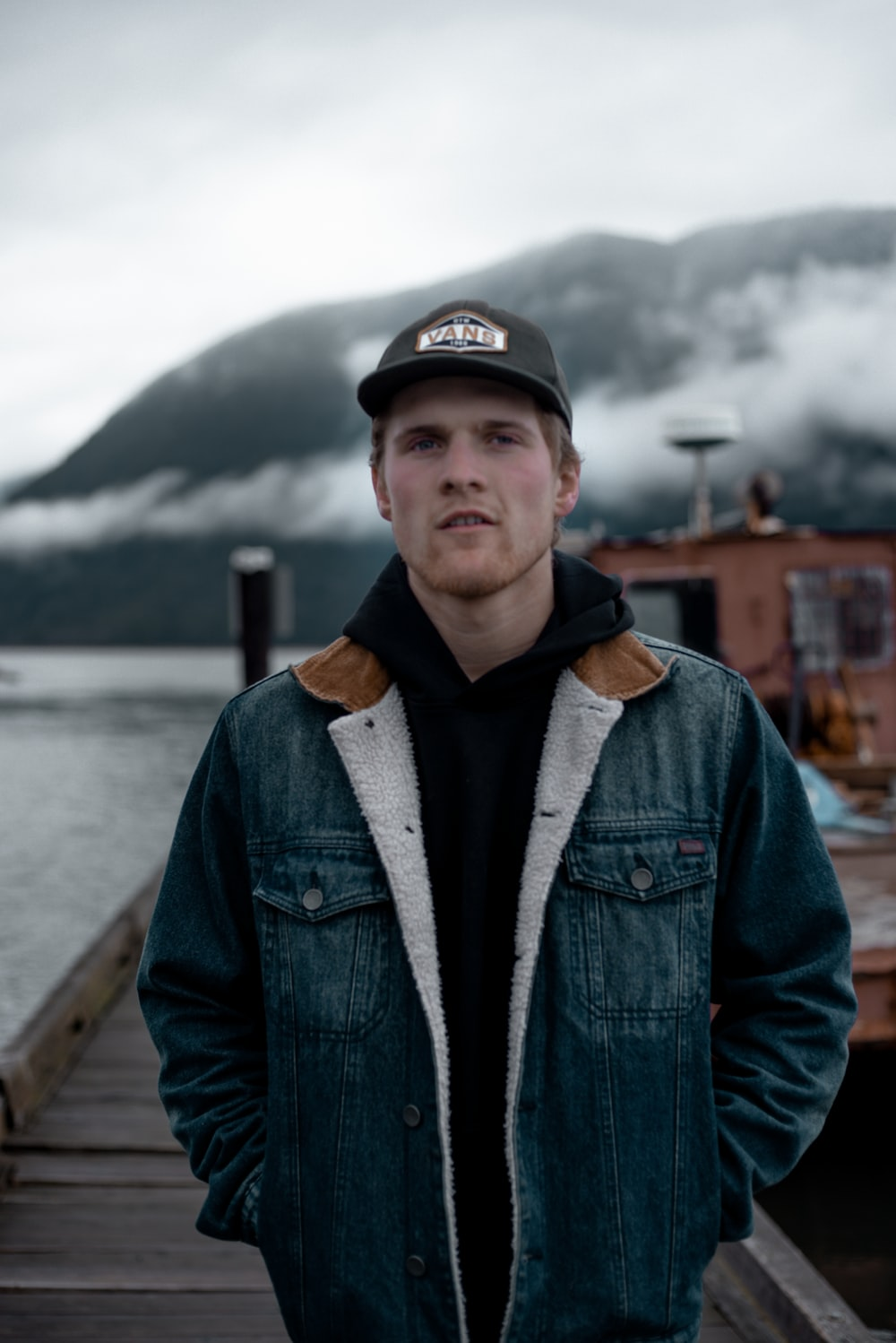 man in blue denim jacket and black cap standing on wooden dock during daytime