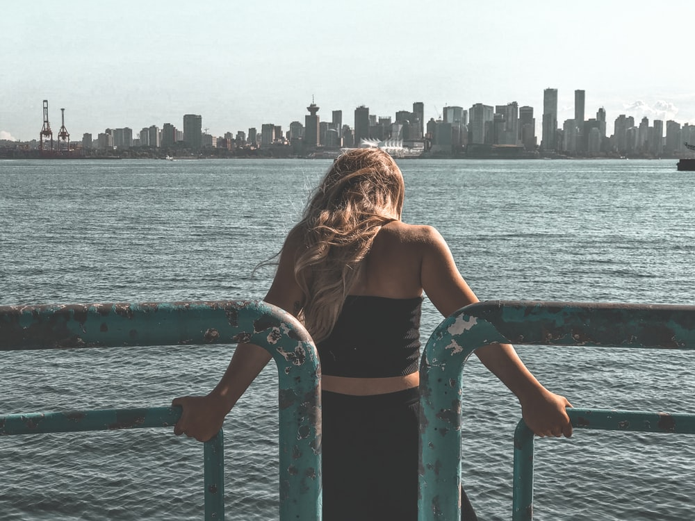 woman in black tank top sitting on blue metal railings near body of water during daytime